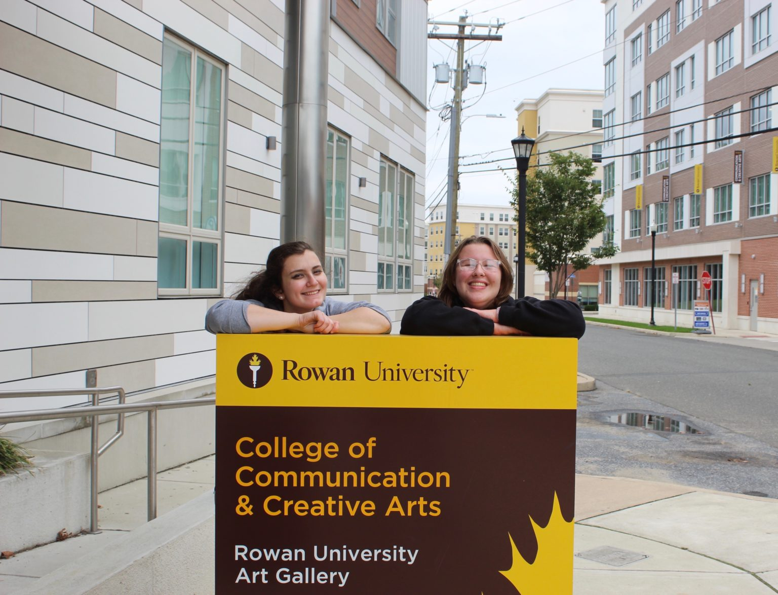 Women students from the Edelman College of Communication and Creative Arts smile in front of the communications building. - Multimedia Editor/ Alexander Rossen