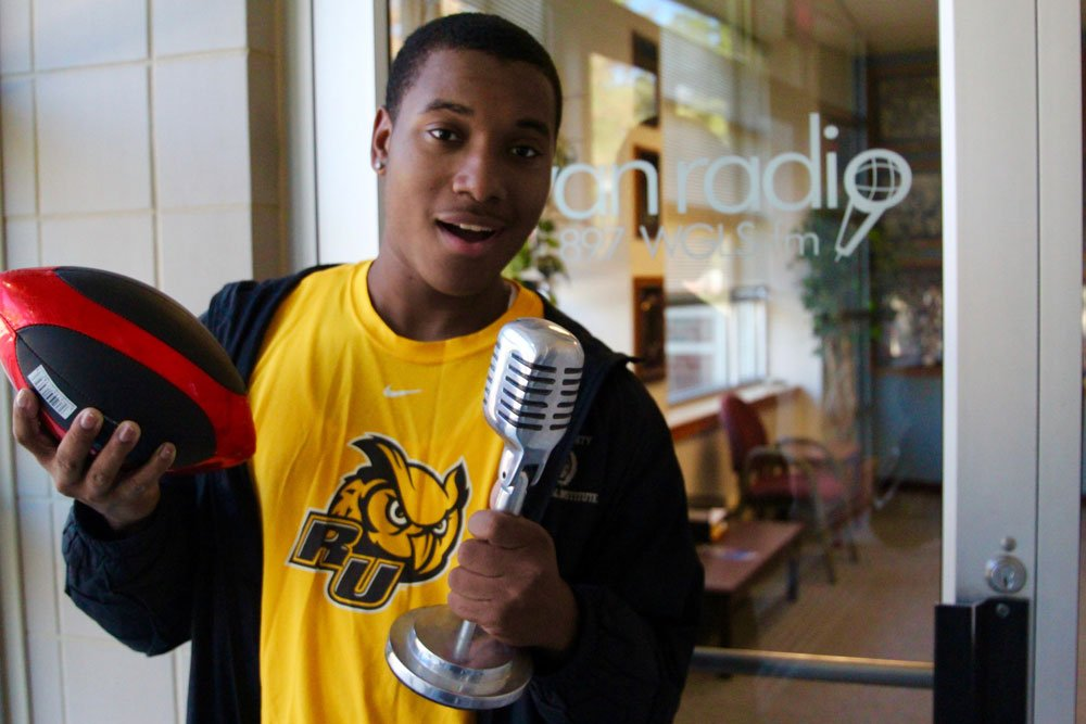 student stands outside of radio station window holding a football and a microphone as if he's talking into it