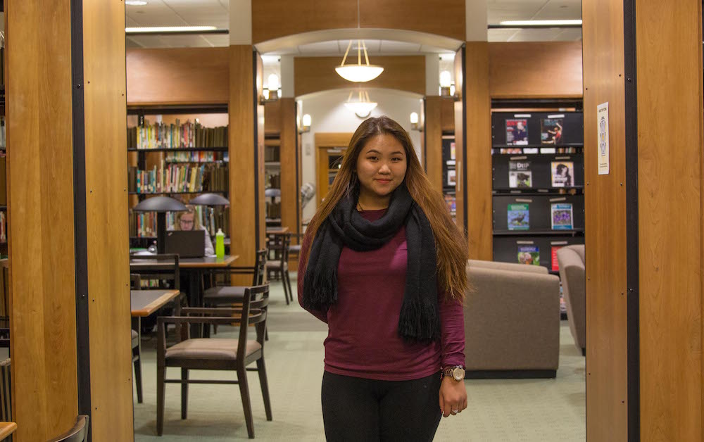 female students stands in the library in between columns of books and magazines