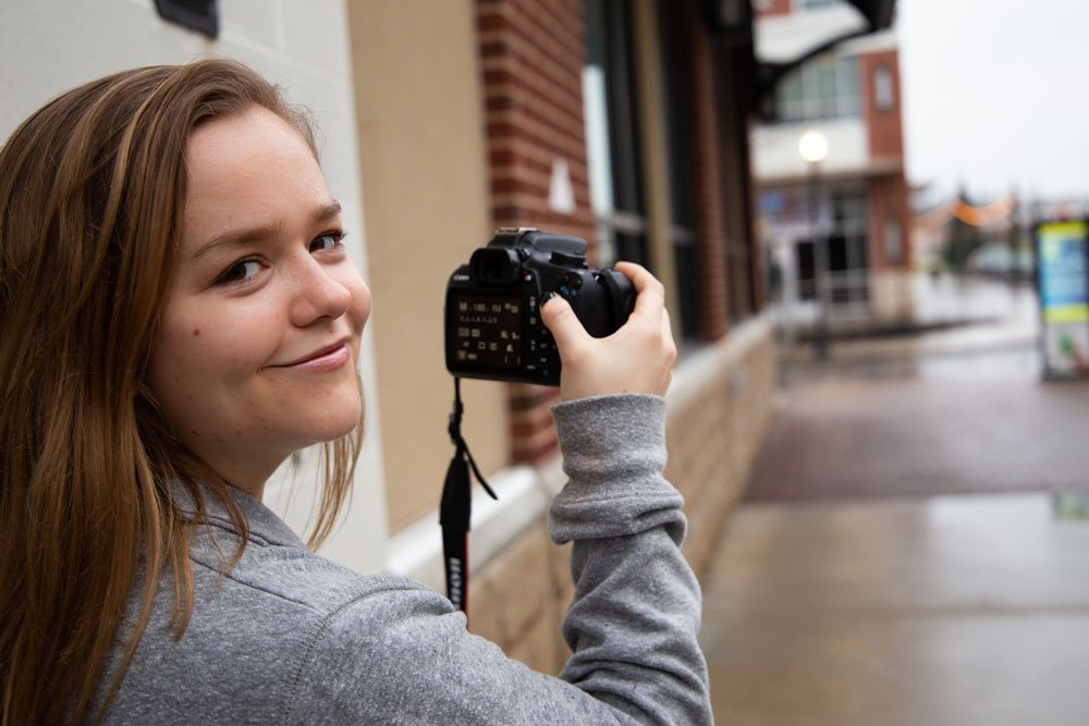 Kailey looks over her shoulder, smiling while holding a camera to take photos on Rowan Boulevard